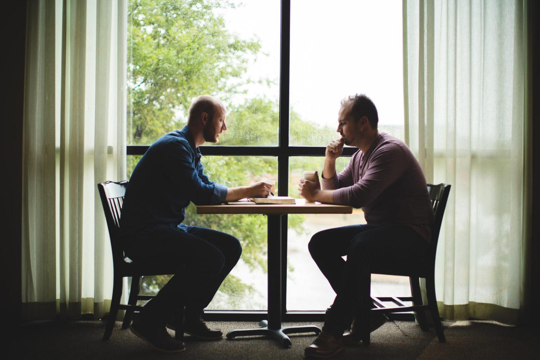 Zwei Personen sitzen sich an einem Tisch gegenüber und reden miteinander.