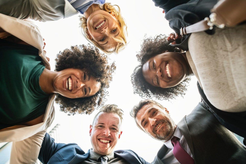 fünf Menschen umarmen sich in einem Kreis