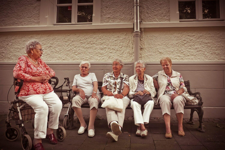 Eine Gruppe Frauen im reifen Alter unterhalten sich im Freien